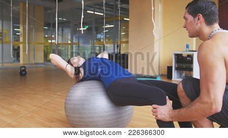Sportive Young Woman With Fitness Instructor Doing Abdominal Crunches On Fitballs, Close Up View