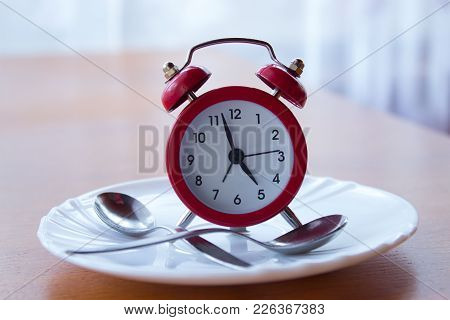 Red Alarm Clock On A Plate With Spoons Stands On A Bedside Table. In The Background  Is A Window Wit