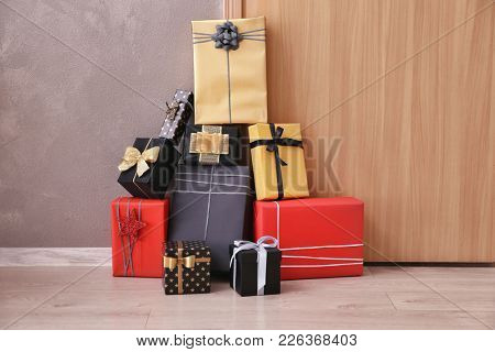 Beautiful gift boxes in front of door indoors