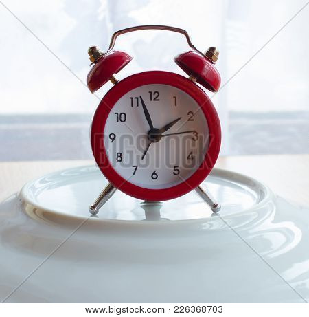 Red Alarm Clock On The Plate. In The Background  Is A Window With Curtain. The Sun Illuminates The S