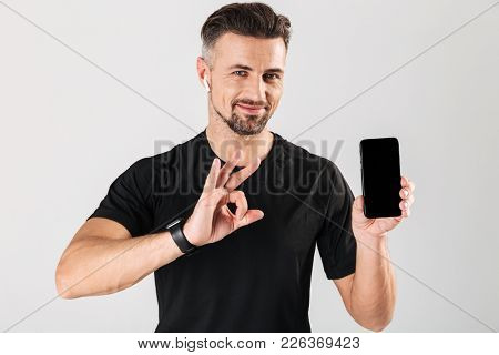 Portrait of a happy mature sportsman showing blank screen mobile phone and showing ok gesture isolated over gray background