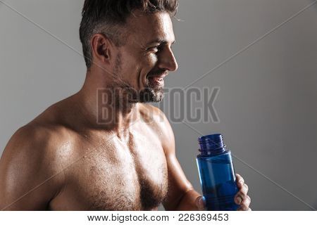 Close up portrait of a smiling mature shirtless sportsman drinking water from a bottle isolated over gray background