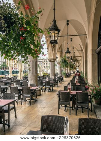 KRAKOW, POLAND - AUGUST 07 2017: Sukiennice arcades with outdoors restaurant tables and chairs, Main Market Square, Krakow, Poland