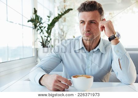 Image of masculine man 30s sitting alone in city cafe with cup of coffee beverage and looking aside with brooding sight
