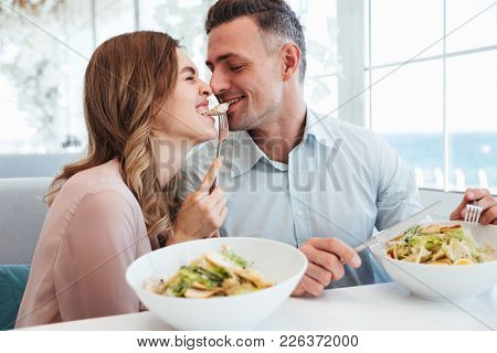 Photo of happy romantic couple having dinner and eating salats together while resting in city cafe during lunch break
