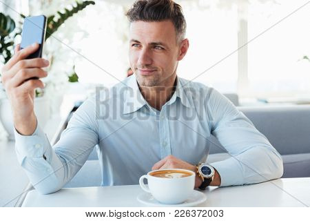 Smiling elegant mature man resting alone in cafe with cup of caffeine beverage and making selfie or photographing on black smartphone