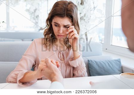Portrait of happy sensual woman 20s being touched and emotional after receiving marriage proposal from her man on date in restaurant