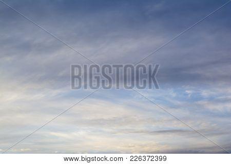 Wispy Translucent Clouds Against Darkening Blue Sky. Background Suitable