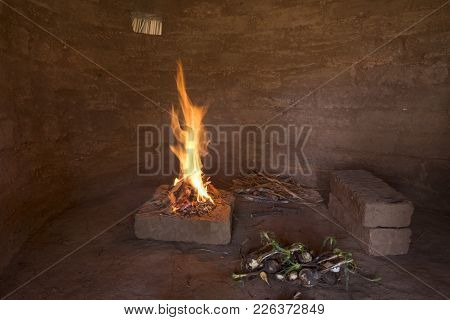 Small Campfire Burning On Bricks Inside Primitive Adobe Hut With Dirt Floor And Wild Soap Plant Root