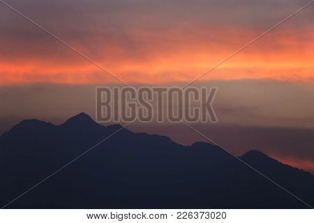 Silhouetted Sunset Sky With The Mountains.beautiful Orange Clouds After Sunset For Background