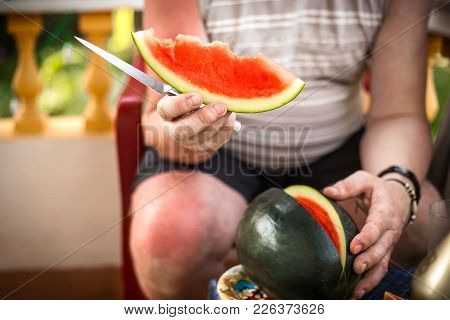 Men Hand Hold From On Fresh Watermelon Cutting For Eatin On Table Background. Male Cutting A Delicio