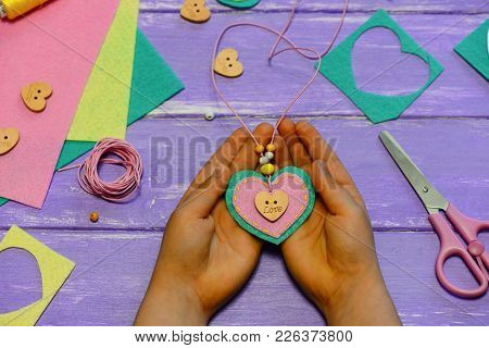 Child Holds A Heart Shaped Pendant In His Hands. Child Made A Heart Shaped Pendant From Felt, Beads