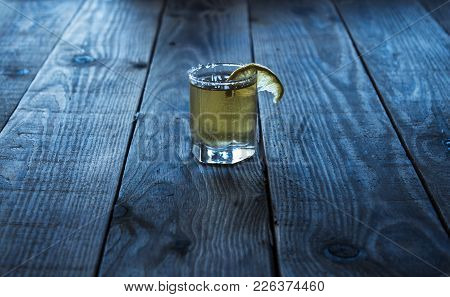 Tequila With Lemon On A Wooden Bacground