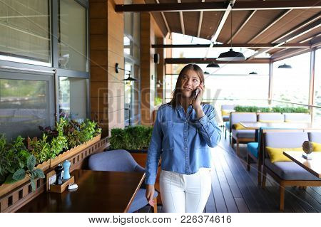 Female Model Talking By Smartphone With Photographer And Negotiating About Photo Session. Young Girl