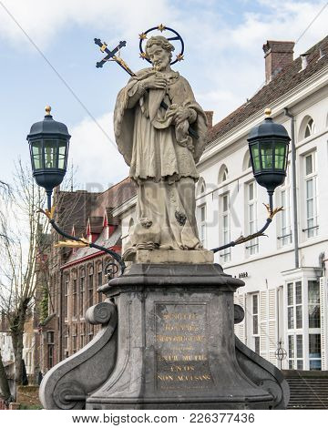 Brugge, Belgium - February 2018: St. John Of Nepomuk, John Nepomucene Statue On Bridge With Tower Of