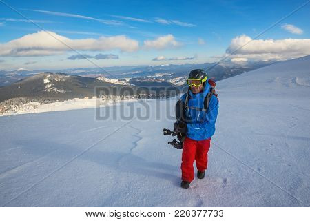 Snowboarder Climbs On A Mountain Ridge, On The Background Of Blue Sky At Sunny Day. Epic Freeride In