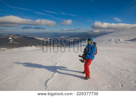 Snowboarder Posing On A Mountain Ridge, On The Background Of Blue Sky At Sunny Day. Epic Freeride In