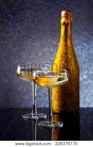 Image of bottle of sparkling wine in gold wrapper with two wine glasses