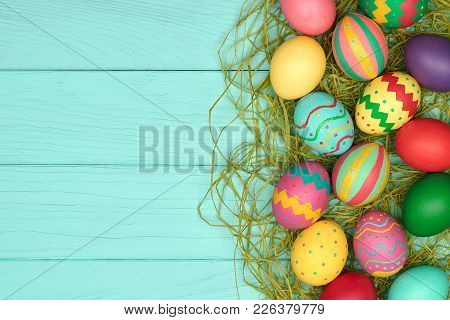 Easter Eggs Background. Hand Painted Colorful Decorated Eggs On Green Straw, Blue Wood.holiday Greet