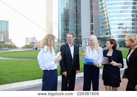Business Employees Talking With Boss In La Defense Paris Keeping Laptop And Document Cases. Concept