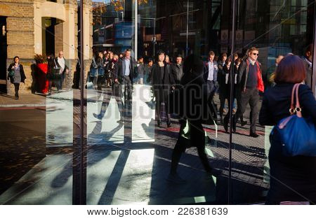 LONDON, UK - NOV 1, 2012: Pedestrians reflecting in an office building window busy city life concept