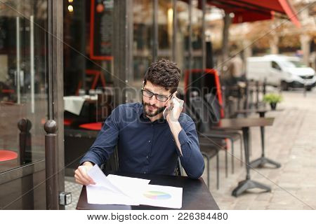 Real Estate Agent Talking With Disgruntled Client By Smartphone At Cafe Table In  .  Annoyed Caucasi