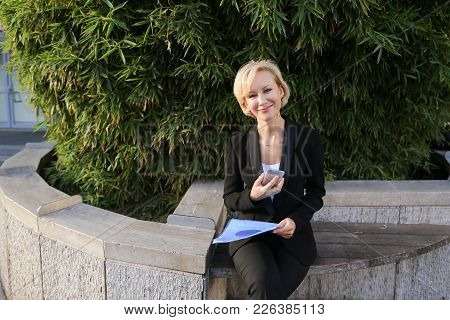 Businesswoman Talking With Partner By Smartphone Outdoors And Keeping Blue Document Case. Concept Of
