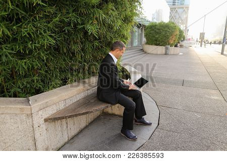 Businessman Typing By Laptop Outside Near Green Plant In   And Looking At Watch. Concept Of Ecology