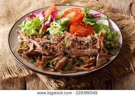Spicy Pulled Beef With Vegetable Salad Close-up On A Table. Horizontal
