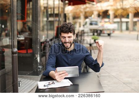 Dissatisfied Man Losing At Online Game Playing With Tablet At Street Cafe. Young Man Has Dark Hair,