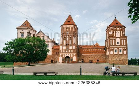 Mir, Belarus - June 25, 2017: Young Family With Baby Sits On Bench And Admires Medieval Castle In Mi