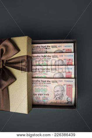 Cancelled Thousand Indian rupee currency notes revealed in a gift box.