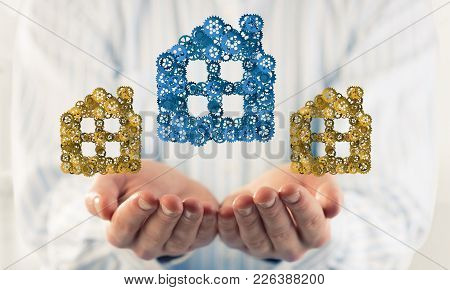 Hand Of Businessman Showing House Or Home Gear Sign In Palm