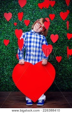 Ð¡ute child boy holding big heart surrounded by little hearts over lawny background. First love. Valentine's Day.