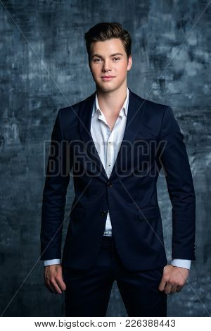 Handsome young man in elegant suit posing over grunge background. Business style. Male beauty, fashion. Hairstyle.