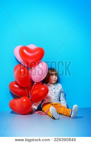 Ð¡ute six-year-old boy holding heart shaped balloons over blue background. Valentine's Day.