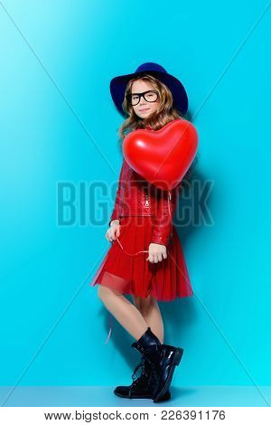 Full length portrait of a pretty pre-teen girl holding heart shaped balloon over blue background. First love. Valentine's Day.