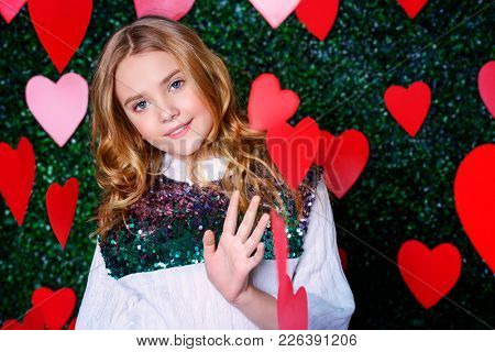 Happy pre-teen girl poses surrounded by little hearts over lawny background. First love. Valentine's Day.