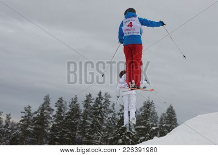 KRASNOE OZERO, LENINGRAD REGION, RUSSIA - FEBRUARY 1, 2018: Ksenia Kuznetsova (blue) of Russia and Frida Lundblad of Sweden compete in dual mogul during Freestyle Europa Cup competitions