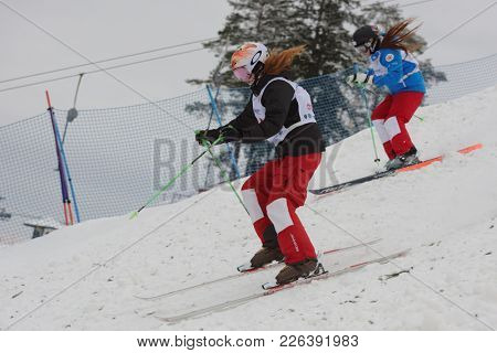 KRASNOE OZERO, LENINGRAD REGION, RUSSIA - FEBRUARY 1, 2018: Yelizaveta Bezgodova (blue) and Anastasia Kulikova, both of Russia, compete in dual mogul during Freestyle Europa Cup competitions