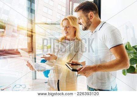 Very Nice. Cheerful Experienced Smart Specialist Pointing To The Screen Of A Modern Laptop While Sta