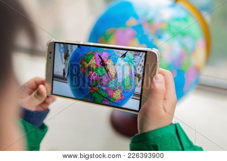 Zhongshan,china-february 7, 2018:kid Playing Augmented Reality Popup Globe With Dinosaurs Via Mobile