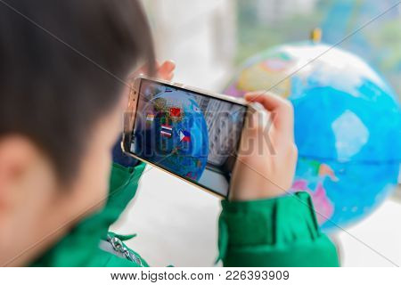 Zhongshan,china-february 7, 2018:kid Playing Augmented Reality Popup Globe With Flags Via Mobile. Ar