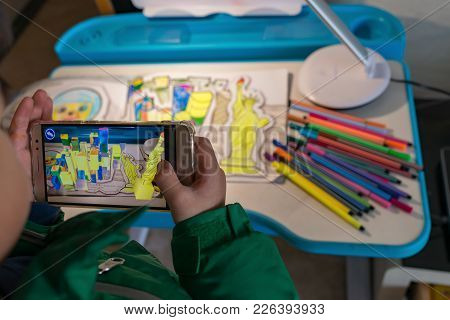 Zhongshan,china-february 8, 2018:kid Playing Augmented Reality Popup Paintings Of A Color Filled Sta
