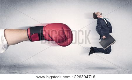 Businessman gets fired from his job by a huge hand in boxing gloves