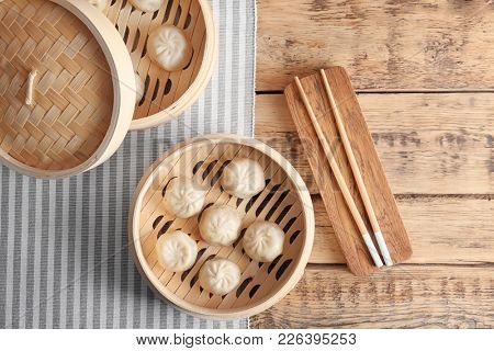Bamboo steamers with tasty baozi dumplings on table