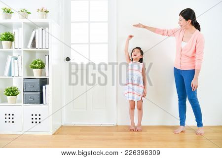 Pretty Attractive Mother With Cute Little Daughter Measuring Growth Record When They Standing In Woo