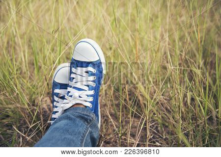 Blue Sneaker, Pretty Woman Wear Jeans And A Blue Sneaker On A Green Meadow.