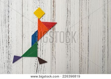 Wooden Tangram Shaped Like A Fast Walking Girl With Things On Hands