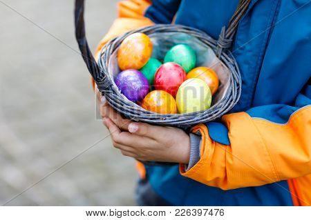 Close-up Of Hands Of Little Child With Colorful Easter Eggs In Basket. Kid Making An Egg Hunt. Child